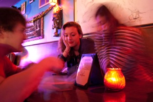 Amy Hersh (Center) stares pensively as her companions, Rio Fraiser (R) and Cody McCloud (L) discuss their beverage orders at A Pizza Mart on the 5000 block of University Way on Jan. 15, 2014
