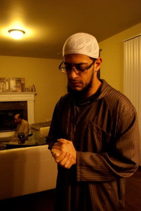 """Mohammad Hammad Ahmed (center) talks about his religion as his father (back left) completes his morning prayers on Feb. 25, 2014 at his home in Bothell, Wash. The sun won't be up for another hour – at 6:57 A.M. But Ahmed has been up for at least a half-hour already. As a Muslim, Ahmed regularly rises before the sun for his morning prayer, even on days when his classes won't start for several hours. He and his father will each complete an individual prayer before doing their Fard – an obligatory prayer - together. """"Faith in my opinion actually goes with family,"""" Ahmed said, """"since you learn and grow together in faith, and this growth is faith leads to sincere love for each other."""""""