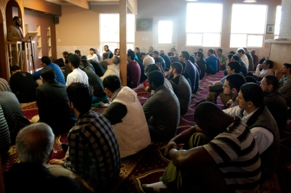 "Mohammad Ahmed (first row, first from left) joins his fellow members of the Muslim Student Association as well as members of his community for ""Jumu'ah"" – Friday Prayers on Feb. 28, 2014 at the M.S.A.'s Islamic House. The congregational leader – called an ""Imam"" – delivers a sermon before leading the group in prayer."