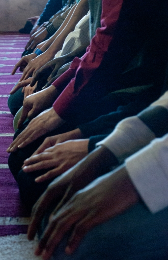 "Members of the Islamic House rest their hands on their knees during a prayer on Friday, Feb. 28, 2014. Muslims' prayers are set to happen a minimum of five times throughout the day and have series of set movements. Completing one set of movements is called a a ""rak'ah."" During prayer, a Muslim will rest on his or her knees then lean forward to press his or her head onto the floor. This act, which represents humility before God, is done twice in a single rak'ah, with members placing kneeling and placing their hands on their knees in between the two."